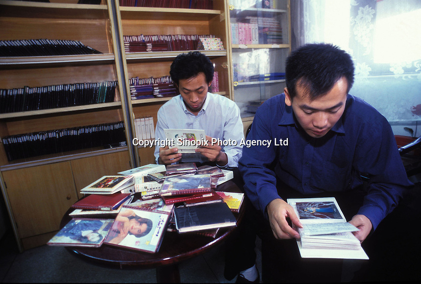 Unmarried men look at books of women for potential brides at the Heart to Heart Dating Agency in Guangzhou, China. An average gender inbalance of 118 males to 100 females caused by the strict One Child Policy and the preference for boys means that there is a shortage of women in China..