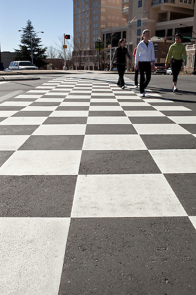 March 6, 2010. Charlotte, North Carolina.. Over the last year, several museums and cultural institutions have opened within a 5 block radius of each other, adding another facet to downtown Charlotte.. Walkers pass over the checkered crosswalks, made to llok like the checkered race flags, that lead to to the soon to open NASCAR Hall of Fame.