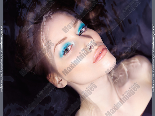 Sensual beauty portrait of a young woman with blue makeup lying in dark water