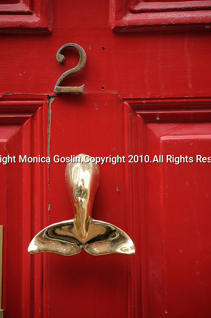 A red door with a gold door knocker in the shape of a whale's tale in Beacon Hill in Boston, MA.