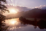 Coos River, Oregon, Inspirational image of rays of sun over pastoral river and hills