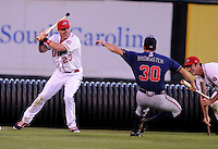 Members of the Rome Braves, including Cory Brownsten (30), right, and Greenville Drive, including Matt Marquis (23), left, stage a mock battle, attacking from opposite sides of the field, during a lengthy rain delay before a game on July 5, 2012, at Fluor Field at the West End in Greenville, South Carolina. (Tom Priddy/Four Seam Images)