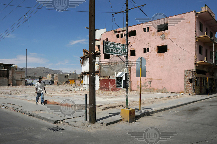 A man walks past a plot where a nightclub used to be in the centre of the city of Ciudad Juarez in the area around Avenida Juarez. The area used to have a lively nightlife, but today it has an ill reputation and is due to be demolished to make way for a shopping centre.