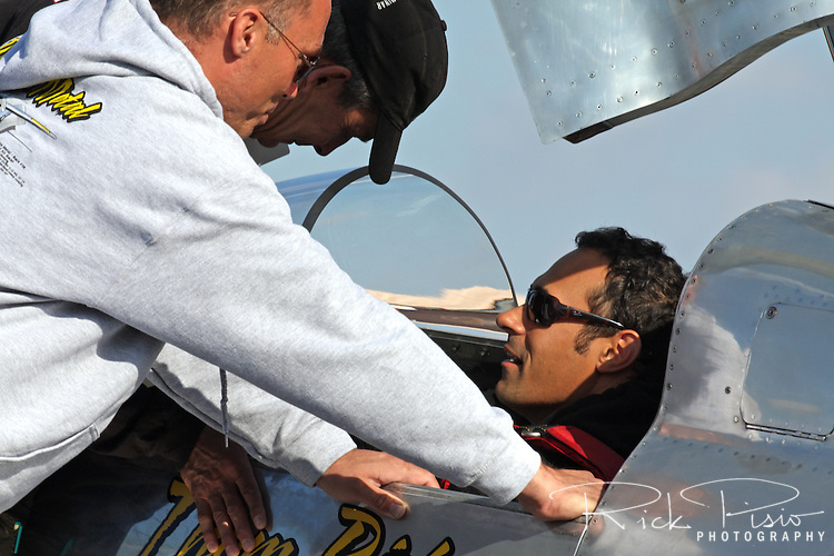 Crew members of the P-51 Air Racer 'Precious Metal' discuss strategy with pilot Thom Richard during the 2011 Reno Air Races.