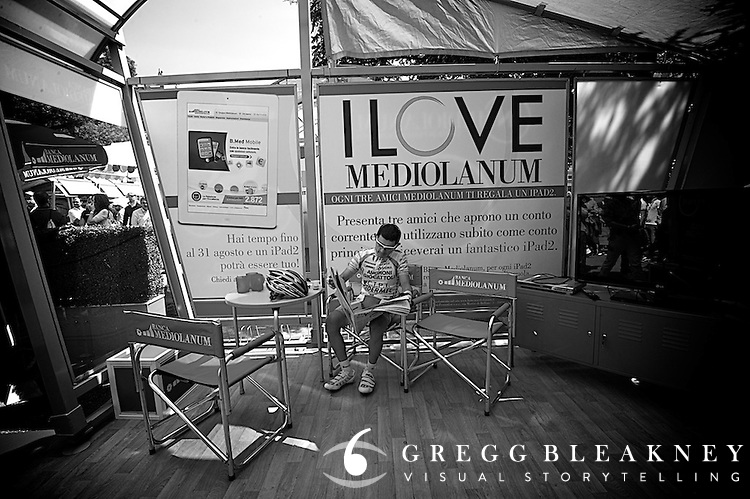 Jose Rujano seems to seek out quit spaces in the minutes before start time.  Here, he relaxes with the morning paper in one of the Giro's few empty media tents.
