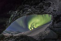 The northern lights are visible from inside a glacier ice cave in the Alaska Range mountains, Interior, Alaska.