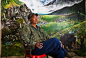 Kama Wangdi (50) poses in front of his paintings commissioned by the Smithsonian Gallery in Washington. Kama runs VAST (Voluntary Artist Studio) and supports and mentors the young artists in Thimphu, Bhutan. Sanjit Das/Panos