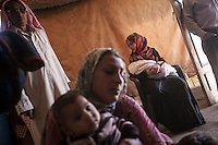 June 11, 2015 - Bekaa Valley, Lebanon: Mariam Edriz (centre) and Hamda Saleh (right bottom) hold their babies as Mariam's father, Nader Ahmal Mohammed (left), is standing in their family tent tent in a temporary shelter settled in Saadnayel city in east of Lebanon. All of them are refugees from Syria who fled years ago when opposition armed groups started battling against the government of President Bashar Al-Assad. (Photo/Narciso Contreras)