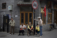 BEIJING, CHINA - SEPTEMBER 30: Elderly Beijing residents sit outside a shop at an old alleyway, or hutong, as they take part in a voluntary scheme to monitor their neighbourhood to ensure the safety of tomorrow's National Day celebration on September 30, 2009 in Beijing, China. Chinese people are in preparation for the upcoming National Day on October 1, 2009 which will commemorate the 60th anniversary of the founding of the People's Republic of China.