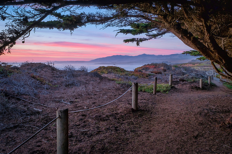 The dramatic colors of dusk dimly illuminate the bluff trail in Leffingwell Landing State Park north of Cambria on California's central coast.