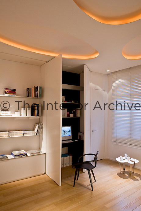 Lacquered cupboard doors in the study conceal a home office