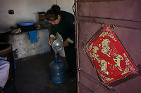 Mongolian herder Renqima prepares Mongol Arkhi, traditional milk liquor, which was fermented from yogurt at her dairy farm in Damao Banner, Inner Mongolia, China, 2014.