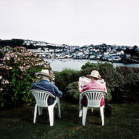 A tourist couple read newspapers in the garden of their hotel in Fowey, overlooking the harbour of Polruan, Cornwall.