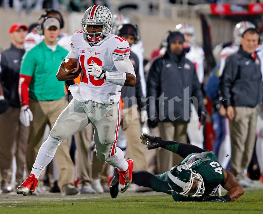 Ohio State Buckeyes quarterback J.T. Barrett (16) carries the ball past Michigan State Spartans linebacker Ed Davis (43) during the 1st quarter at Spartan Stadium in East Lansing, Michigan on November 8, 2014.  (Dispatch photo by Kyle Robertson)