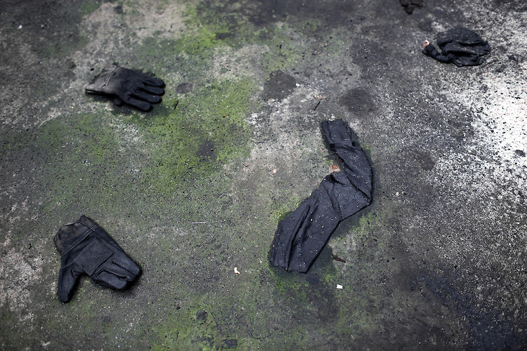 Remains of clothing used by the workers scattered around the garage floor in Pen?arol, Montevideo, Uruguay.