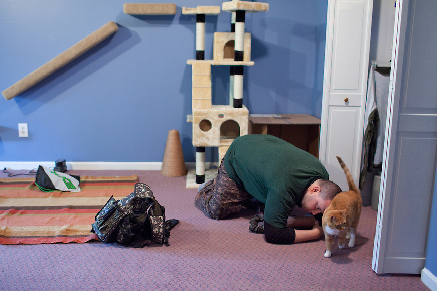 Stephen Yunis plays with his cat, Nala, at his home in Germantown, Maryland on May 18, 2013. Mr. Yunis jokes that taking care of three cats with his wife has prepared them for having a child. His wife, Jenn Yunis, has finally become pregnant after many attempts, with the help of Shady Grove Fertility Center in Rockville, Maryland.