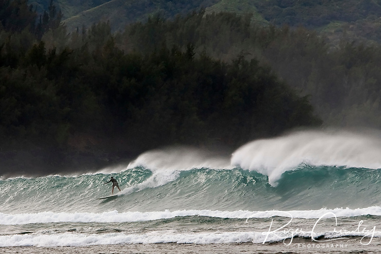 A surfer rides a large wave on Ke'e Beach in Hanalei Bay on the island of  Kaua'i, Hawaii