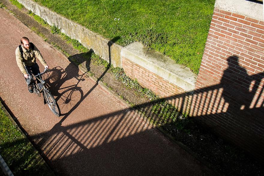 Nederland, Utrecht, 5 maart 2014<br /> Fietsende man rijd over een fietspad, gadegeslagen door de schaduw van een man. <br /> Foto(c): Michiel Wijnbergh
