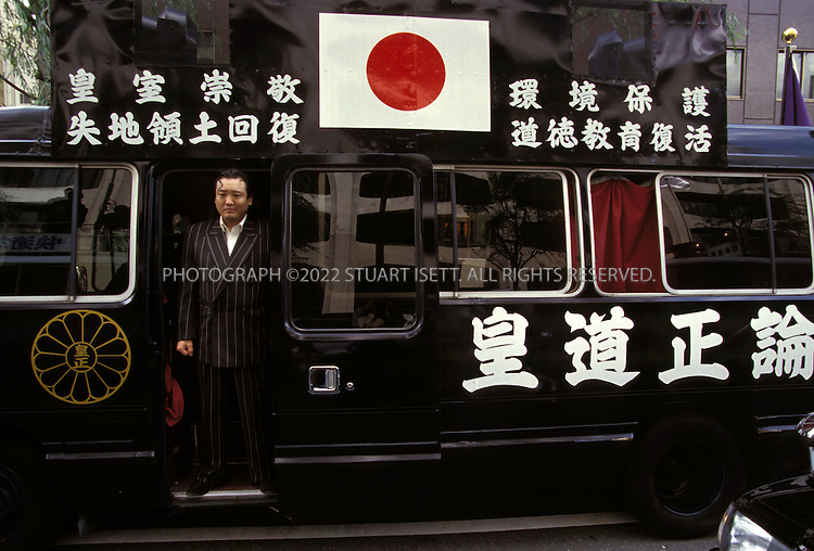 8/16/02--Tokyo, Japan..A rightwinger and yakuza stands in the door of a sound truck...All photographs ©2003 Stuart Isett.All rights reserved.This image may not be reproduced without expressed written permission from Stuart Isett.