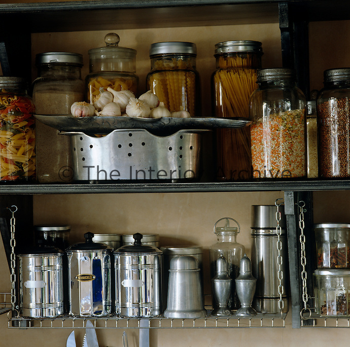 Glass and metal jars filled with pasta and pulses are stored on an open kitchen shelf