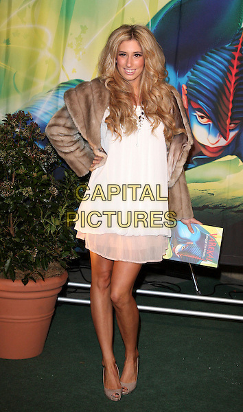 STACEY SOLOMON.Attending the Gala VIP Opening Night of Cirque du Soleil's 'Varekai' at the Royal Albert Hall, London, England, UK, .January 5th 2010..arrivals full length white layered dress brown cropped fur jacket hand on hip   tanned bare legs sun tan beige peep toe grey gray  shoes .CAP/ROS.©Steve Ross/Capital Pictures.