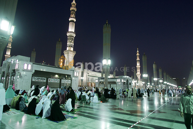 Muslim pilgrims walk outside the Prophet Mohammed Mosque in the Saudi holy city of Medina on November 3, 2010. More than three million Muslims are expected to converge on the holy cities of Mecca and Medina in western Saudi Arabia for the hajj which peaks this year during November 25-29. Islam's Prophet Mohammed is buried in Medina's landmark mosque, which is Islam's second holiest shrine after Mecca . Photo by Mahfouz Abu Turk