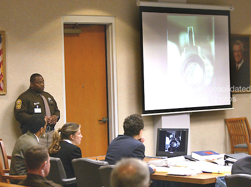 Sniper Suspect John Allen Muhammad, seated left, looks at an image of a gun barrel that is projected on a screen during his trial in Virginia Beach Circuit Court in Virginia Beach, Virginia, November 6, 2003. <br /> Credit: Tracy Woodward - Pool via CNP