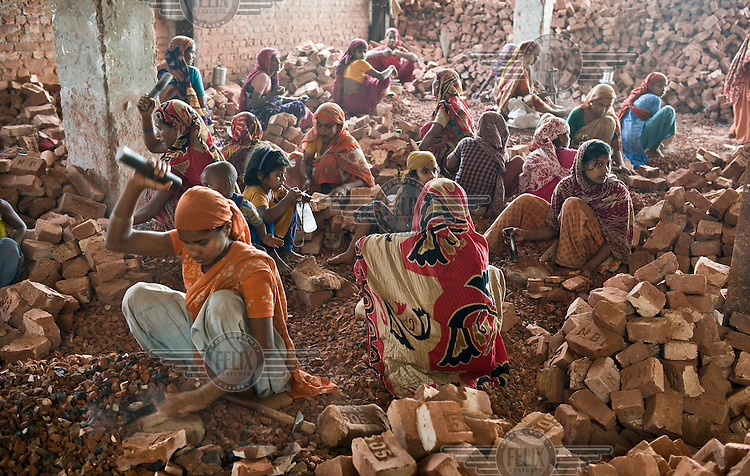 Women and children work breaking up brick and stone into ballast to be used in concrete. Many children are employed in this work, earning between 25-50 Euro cents a day.