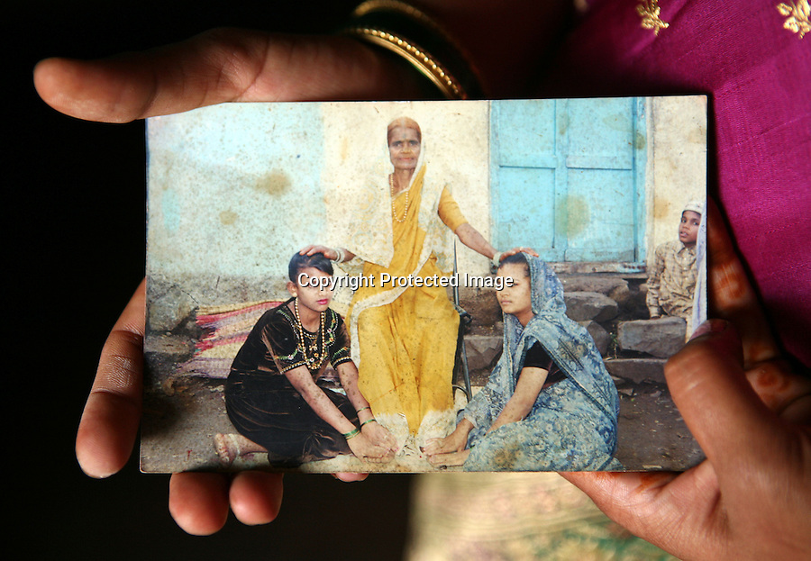 Surekha Kamble holds a photograph of her mother, sister and herself (seated right) taken around the time she and her sister became Devadasi sexworkers in Miraj's redlight district. Since their mother was a Devadasi sexworker, according to Devadasi tradition, she and her sister too were expected to became Devadasi sexworkers.  Kamble's own two daughters, Chandrike and Ropani, are both being educated at a residential school for the children of Devadasis and she has hopes that they will not follow her into the Devadasi lifestyle.