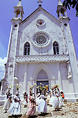 Itaparica, Brazil. Religious ceremony - Washing the Churches; Bahiana women with flowers on their heads outside church.