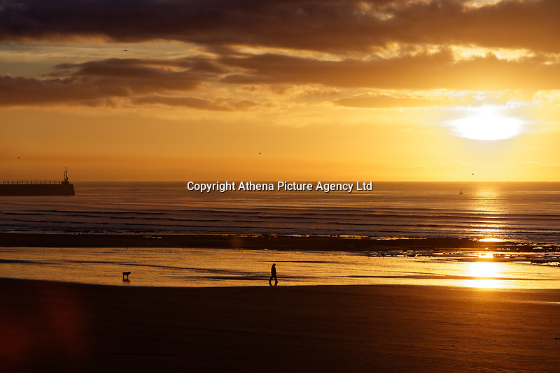 A man walks his dog as the sun rises during an early frosty morning in Swansea, Wales, UK. Tuesday 12 December 2017