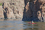 .Howie Wallace paddles Necky Looksha Sport sea kayak beside basalt cliffs in John Day River canyon at RM 96.5.  Clarno to Cottonwood Bridge Section
