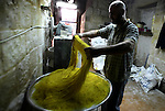 A Palestinian cook prepares the typical Palestinian sweet Kanafeh, a Levantine cheese pastry soaked in a sweet sugar-based syrup, in the West Bank City of Nablus, on April 27, 2014. The pastry is heated in butter, margarine, or palm oil, then spread with soft white cheese, such as Nabulsi cheese, and topped with more pastry. Photo by Nedal Eshtayah