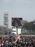 Spectators watch the ceremony on an outdoor screen as they brave the cold winter weather to attend the inauguration of US President Barack Obama, Tuesday, Jan. 20, 2009, in Washington, D.C. (Tricia Buchhorn/pressphotointl.com)