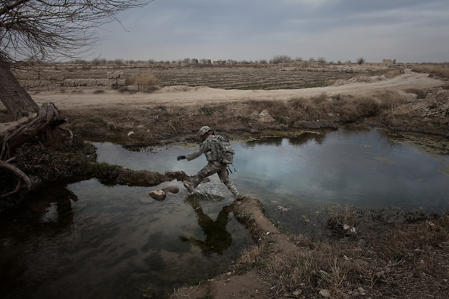 A soldier with Charlie Co. 1st Battalion 12th Infantry Regiment, 4th Infantry Division leaps an irrigation ditch in Zhari District, Kandahar, Afghanistan during a patrol on Jan. 23, 2010. The violently contested district sits astride the strategically Highway 1 ringroad between Kandahar and Lashkar Gah and is seen by some as the birthplace of the Taliban movement.