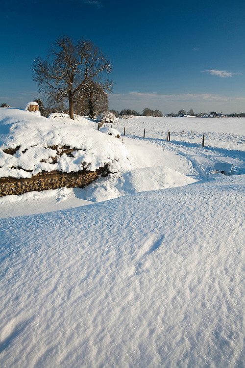 Snow covered Roman Wall looking towards St Mary the Virgin Church, Silchester, Hampshire, Uk