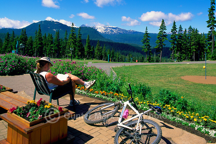Mount Washington, Vancouver Island, BC, British Columbia, Canada - Cyclist sitting in Chair and reading beside Bicycle