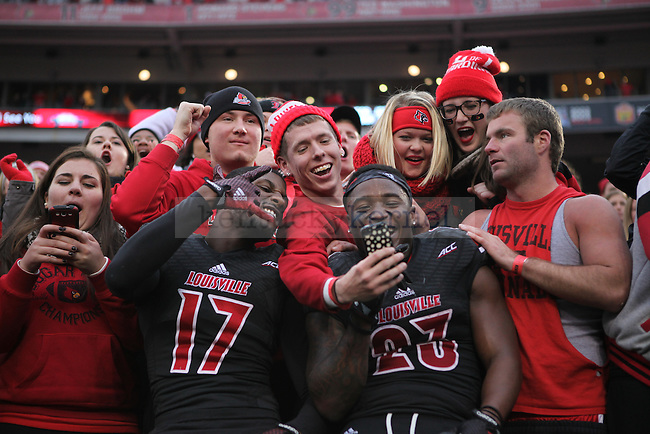 UL wide receiver James Quick, left, and running back Brandon Radcliffe pose with fans after winning the University of Kentucky vs. University of Louisville at Papa Johns Cardinal Stadium in Louisville, Ky., on Saturday, November 29, 2014. UL won 44 - 40. Photo by Tessa Lighty | Staff