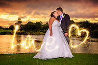 Bride and Groom kissing at Sunset overlooking the lake at Mill Green Golf Club