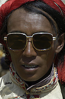 Modern sunglasses in contrast with the traditional ways..Traditional Tibetan dress up in their finest and wearing their most precious Jewelry during this festival. The most common gem stones are worn in the jewelry are Turquoise and red coral..Changtang Chachen Horse Race Festival (August 10th) is the most important festival in northern Tibet during the golden season on the grassland. Thousands of herdsmen throng to Nakchu riding fine horses and carrying local products. They erect a tent city south of Nakchu town. They celebrate with a thrilling horse race, archery contests, and demonstrations of horsemanship. Song-and-dance troupes from all parts of Tibet add to the festivity. It is said that this is the highest horse racing festival in the world, at 4800 meters.