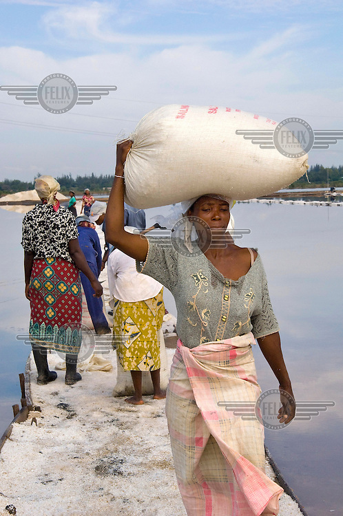 A labourer carries a large bag of salt on her head gathered from a salt pan in Matola.