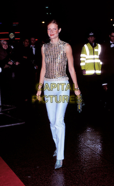 GWYNETH PALTROW..Ref: 9343 ..light blue leather trousers, smiling, brunette, gold top, full length, full-length ..www.capitalpictures.com..sales@capitalpictures.com..©Capital Pictures