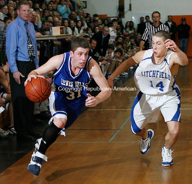 Lewis Mills' Mike Hart drives by Litchfield's Mike Hart during the Berkshire League basketball semi-finals at Terryville High School Wednesday evening. Litchfield won 40-32. Michael Kabelka Republican / American.