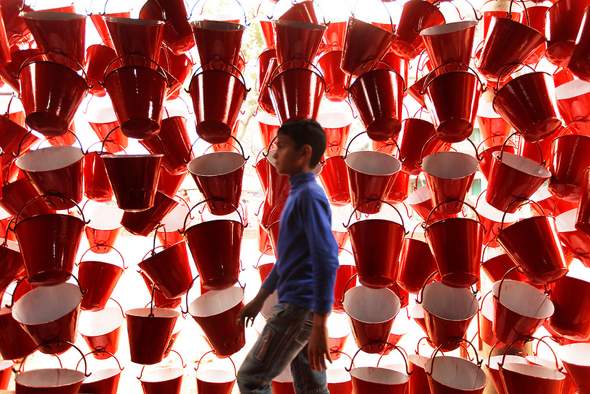 A young Bangladeshi boy walks past a display of aluminum buckets for sale on a street in Dhaka, Bangladesh. The buckets are used in case of fire at garment factories.