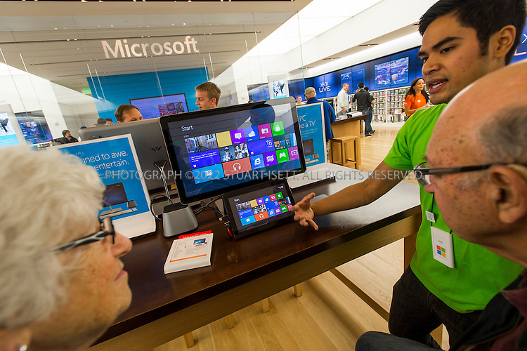 "10/18/2012--Bellevue, WA, USA..At Microsoft's store at the Bellevue Square Mall in Bellevue, WASH., employees made Windows 8 available for customers to see and use on a tablet in the store. ..HERE: Store employee Chris  San Mateo  explains the new operating system to Fred (right) and Rochelle (left) Casserd...NOTE: THE TABLET HAS BEEN CONNECTED TO A LARGER MONITOR, IT IS NOT RUNNING ON A DESKTOP COMPUTER...Microsoft's new Windows 8 operating system is the most radical change to the look of the software most people use on their PCs since the late 1980s. The ""Start"" menu is gone. Programs like the Web browser no longer have traditional menus. Everything looks much more like what you might see on a smartphone or tablet. Microsoft is making the change in part because it is desperate to catch up with Apple and its iPad. But the boldness of the changes could cause headaches among consumers and businesses that buy Windows 8 computers.  ..©2012 Stuart Isett. All rights reserved."