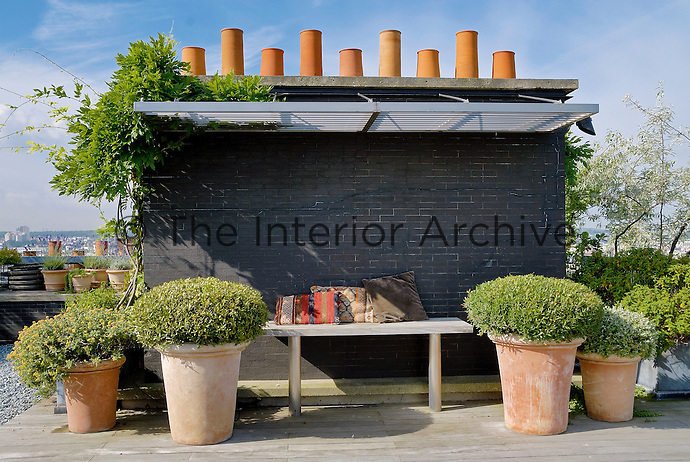 A brick wall, painted black, acts as a windbreak and the chimney pots behind have become a sculptural focal point of this roof garden