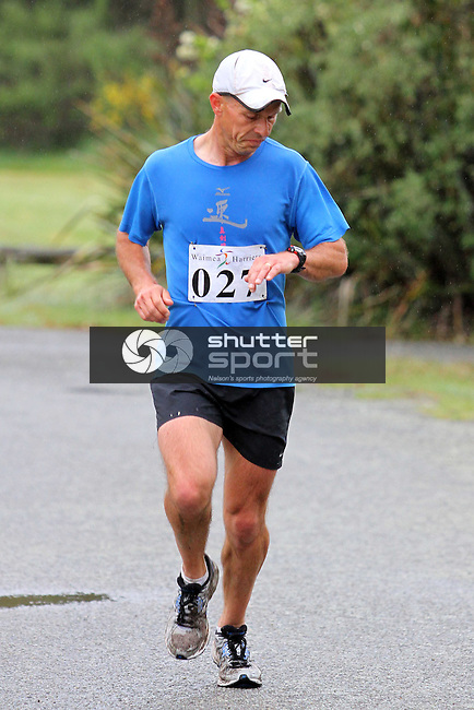 Brian Kemp checks his time as he crosses for thrid overall and 2nd in the 35+ Masters Half Marathon, Rabbit Island, SI Masters Games, 22 October 2011, Nelson, New Zealand<br /> Photo: Marc Palmano/shuttersport.co.nz