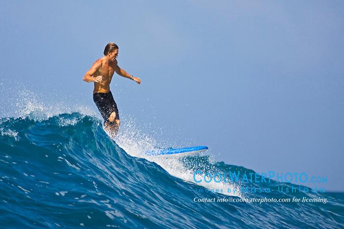 Surfer, enjoying riding rare big ocean waves in Kona Coast, Keauhou Bay, Big Island, Hawaii, Pacific Ocean.