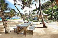 A beach house in a tropical setting with a wooden table and bench seats on the beach provide a place for outdoor dining.