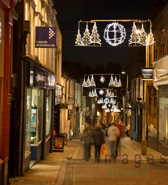 Shoppers walking under Christmas lights down Friars Vennel in Dumfries town centre Scotland